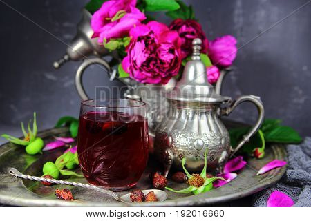rosehip tea on a silver platter with a bouquet of flowers