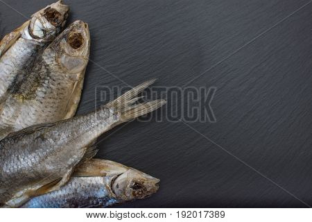 Dried Salted Roach On Black Background Of Slate Or Stone.