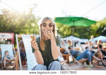 Lady eating ice cream laughing. Portrait of young female sitting in a park on a sunny day eating icecream looking at camera wearing glasses.