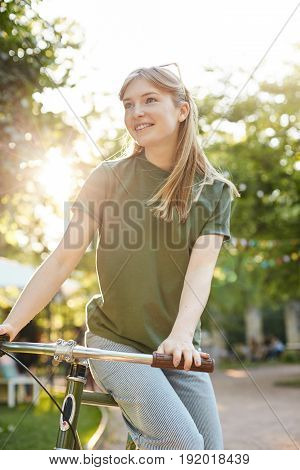 Girl sitting on a bike. Portrait of young woman in city park riding a bycicle looking off camera wearing shades on a sunny summer evening.