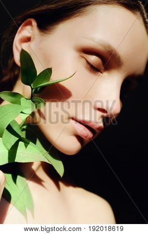 Portrait of a beautiful young woman with green leaf in his hand in the studio, the concept of beauty and health