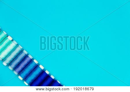 Set of colorful sewing spools isolated on blue background