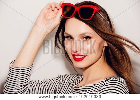 High fashion look.glamor stylish beautiful young happy smiling woman model with red red sunglasses