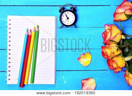 Empty notebook and colorful pencils top view