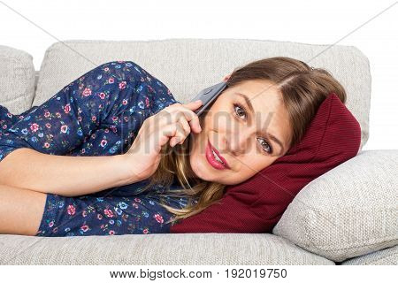 Picture of an attractive young woman lying on the couch having a phone call