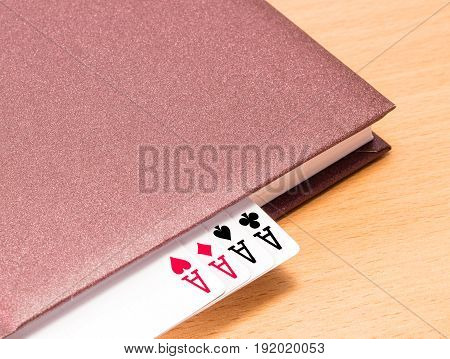 Four aces look out from a brown solid diary with a hard cover this combination in this case symbolizes success in business