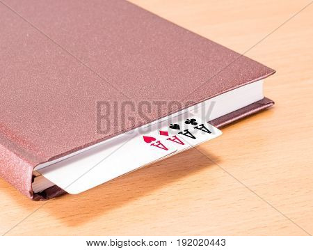 A strong combination for your business is referring to success in your affairs four aces in a solid brown diary on a wooden background