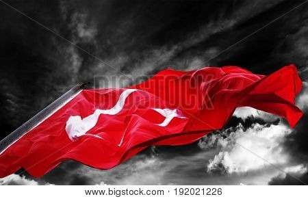Flag of Turkey waving against black and white sky with dark storm clouds