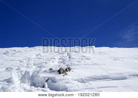 Top Of Snowy Mountains With Footpath And Blue Sky