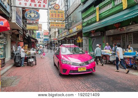 BANGKOK, THAILAND - FEBRUARY 24, 2016: Pink taxi cab in Chinatown in Bangkok. Chinatown is a major tourist attraction in Bangkok famous for its markets and gold shops..