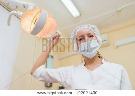 Portrait of young female dentist wearing surgical mask while holding dental lamp.