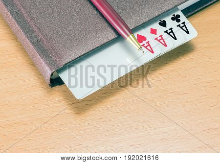 Solid accessories for your business on a wooden background red pen with golden tip brown diary in hardcover and four aces symbol of success