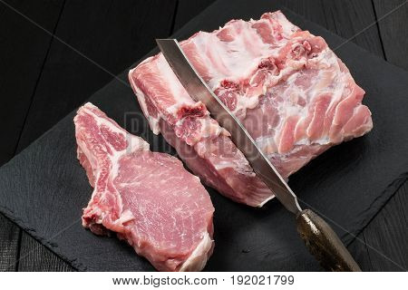 Fresh raw pork loin knife on slate plate. Meat prepared for barbecue roasting stewing. Dark wooden background