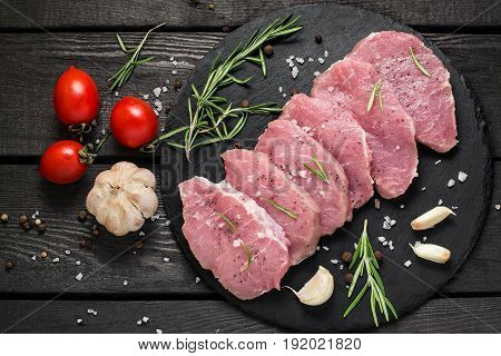 Fresh uncooked boneless pork chops on a slate plate vegetables herbs and spices on a dark wooden background. Meat prepared for cooking