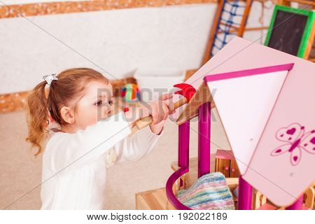Pretty girl repairs the roof of dollhouse in the kindergarten