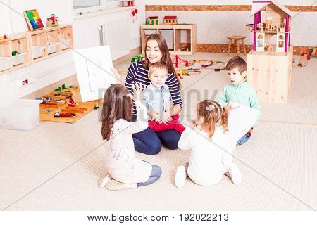 Beautiful young teacher showing letter preschoolers, children sit in a circle