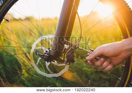 Man Screws The Front Wheel With Hydraulic Disc Brake On The Mtb Bicycle.