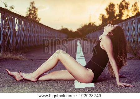 portrait of young woman in swimsuit posing in the middle of an empty road