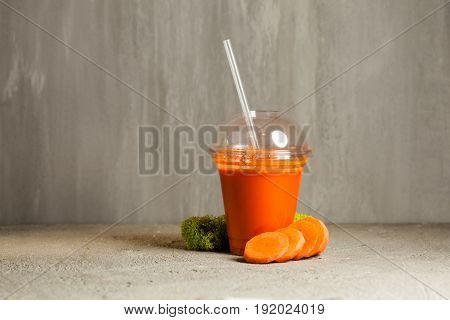 Plastic cup of carrot juice near with fresh vegetables