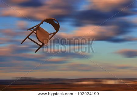 Chair flying in the sky. Brown - orange chair motion on blurred background. Yellow pink clowds. Concept: speed-up, velocity