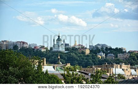 KIEV - UKRAINE - JUNE, 2017: Panorama of Kiev. A view of St. Andrew's Church on the background of the sky and beautiful clouds. High green trees, the center of the capital of Ukraine