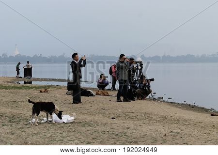 U-BEIN BRIDGE/AMARAPURA, MYANMAR JAN 22:Tourists are waiting at the shore of Taungthaman Lake for the sun to rise over U-Bein Bridge to capture it in the golden hour January 22, 2016, U-Bein bridge/Amarapura.