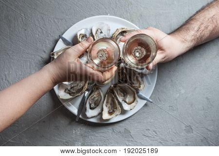 Delicious oysters with slice of lemon and glasses of white wine, top view
