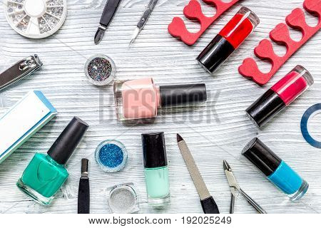 nail artist desk with manicure set and nail polish for hands care on light wooden background top view