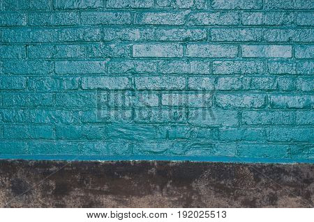 Vintage texture of old brick wall dyed in turquoise color. Painted facade of apartment house