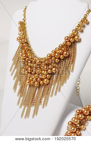 Beautiful gold necklace and bracelet on a mannequin in front of white background