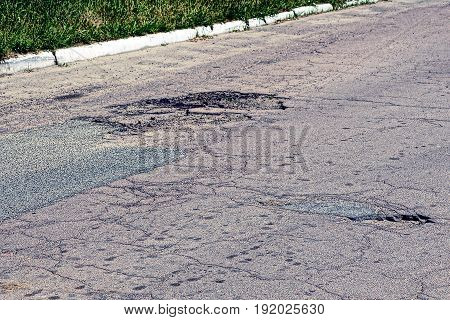 Pits and cracks on an asphalt road in the sunny day
