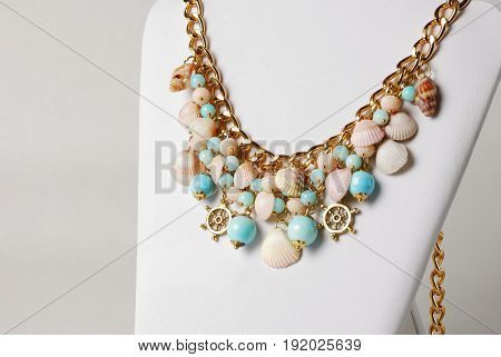 Beautiful necklace in marine style with seashells, and little wheels in front of white background