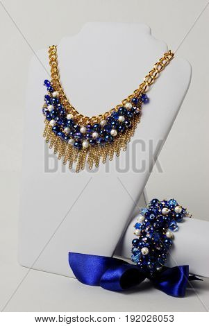 Beautiful navy blue necklace and bracelet on a mannequin in front of white background