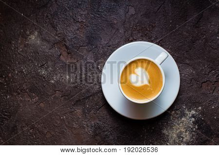 Latte art heart in cup of cappuccino. Top view on brown concrete background