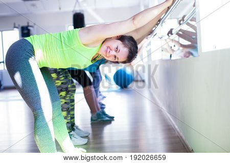 Women doing stretching using the metal railing in the gym