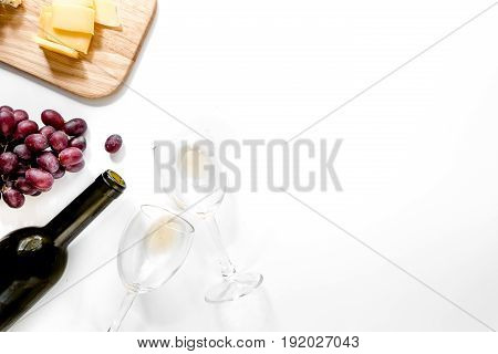 Set for drinking wine with cheese and red grape on white background.