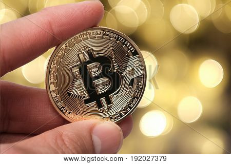 Hand Holding Golden Bitcoin Isolated On Abstract Background