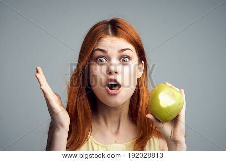 Surprised woman with apple, diet, healthy eating, woman eating apple on gray background.