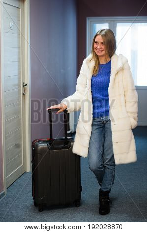 Pretty Young Blonde Woman Traveling Wearing a coat, jeans pulling a suit case.