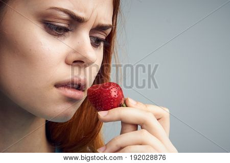 Strawberry, woman looking at a strawberry on a gray background portrait.
