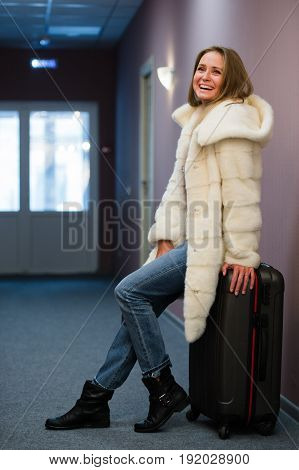 Young woman waiting for a journey at hotel hall