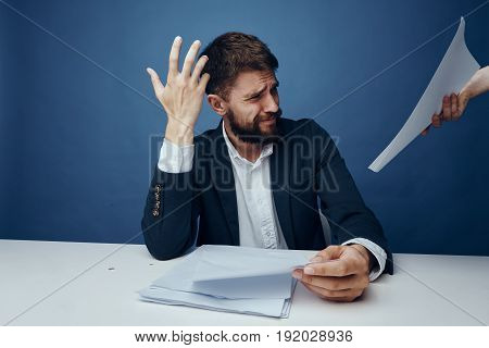 Businessman is not pleased, businessman with documents, businessman on blue background.