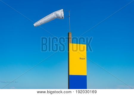 Extended Windsock And Beach Sign Against Blue Sky On The Background
