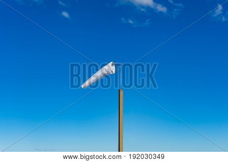White Extended Windsock On Wooden Pole Against Blue Sky On The Background
