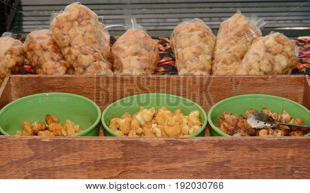 Samples of fried cornmeal fritters dipped in spicy caramel sauce a farmer's market