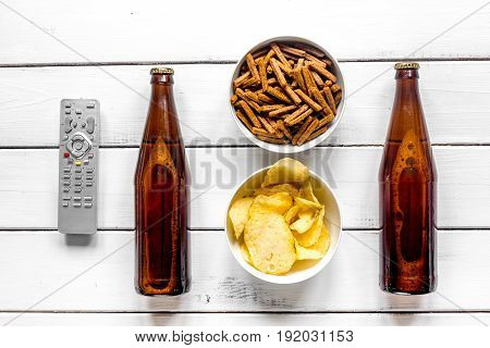 film whatching party with beer, crumbs, chips on white wooden background top view