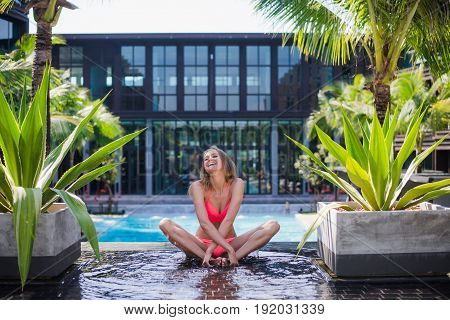 Lifestyle bright summer portrait of sexy beautiful woman with nice body, relaxed at the pool on her vacation