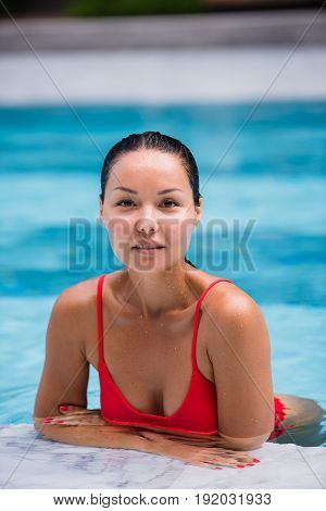 Portrait of beautiful, young lady in red bikini sitting poolside in luxury hotel.