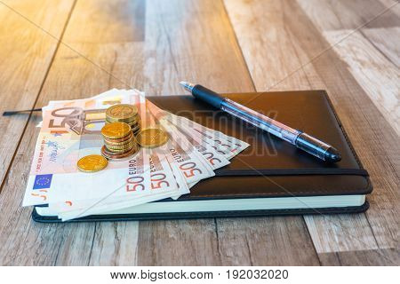 Money euro coins and banknotes on brown wooden background money concept