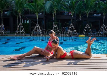 Two attractive blonde and brunette girls with long hair are lying on floor near pool. They wear bikini swimsuit.